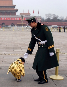 A paramilitary policeman stops a toddler from crossing a restricted area at Tiananmen Square, opposite to the Great Hall of the People, the venue of the National People's Congress or parliament, in Beijing